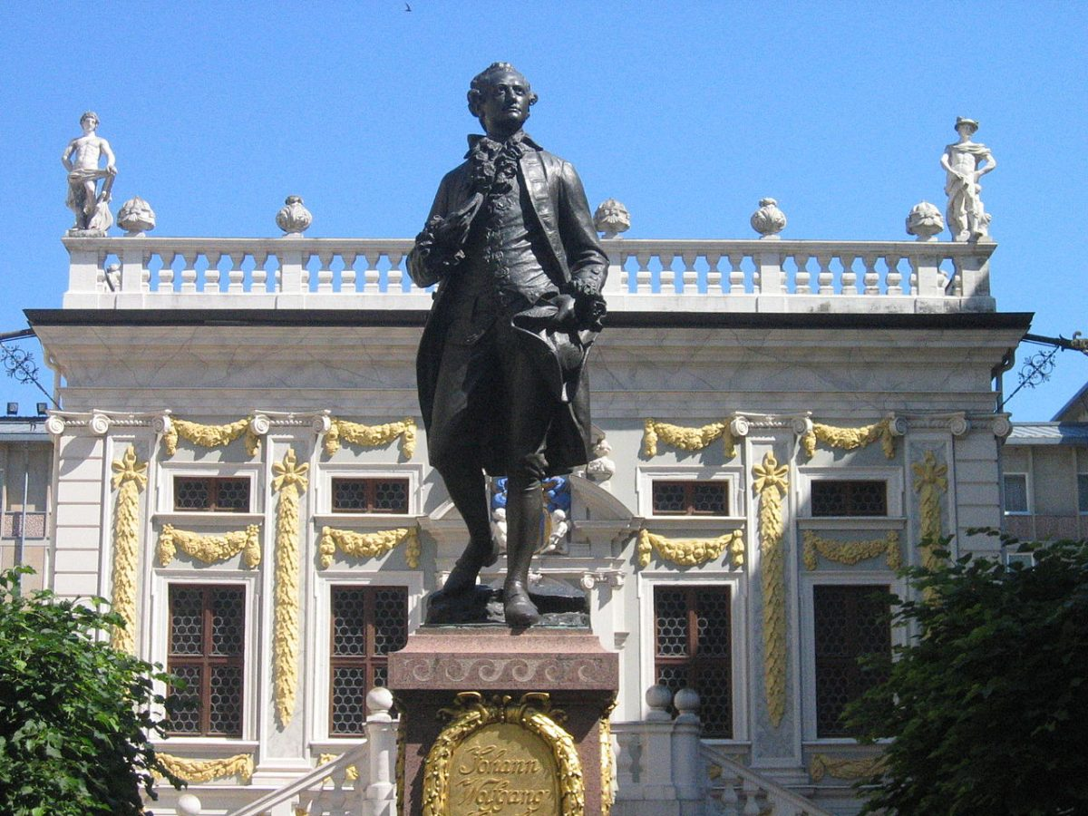 Goethe Statue in front of Alte Börse at the Naschmarkt in Leipzig / Der junge Goethe von Carl Seffner vor der Alten Börse/Naschmarkt, Leipzig [photo: jpvargas, CC BY-SA 2.0 https://creativecommons.org/licenses/by-sa/2.0, via Wikimedia Commons]